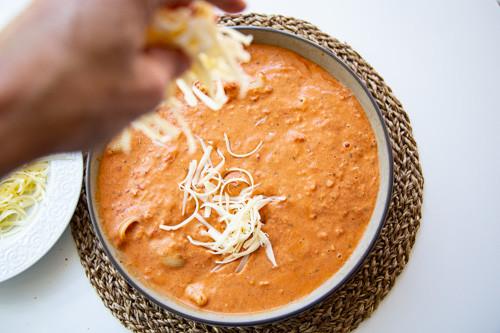 Pampered Chef runde Stoneware Sauce auf Nudeln verteilt und Käse drüber